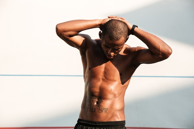 Portrait of a handsome african sports man with hands behind the head, resting after workout