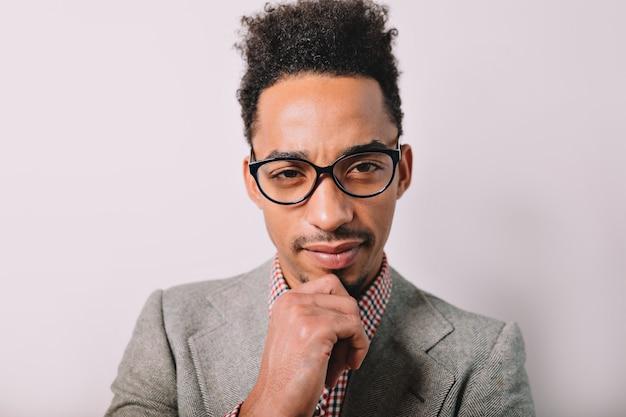 Ritratto dell'uomo alla moda afroamericano bello indossa occhiali e giacca su grigio con un sorriso adorabile