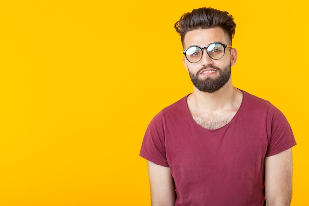 Portrait of a handsome arab young male student in burgundy shirt posing on a yellow wall with copy space. concept of opportunity for young people