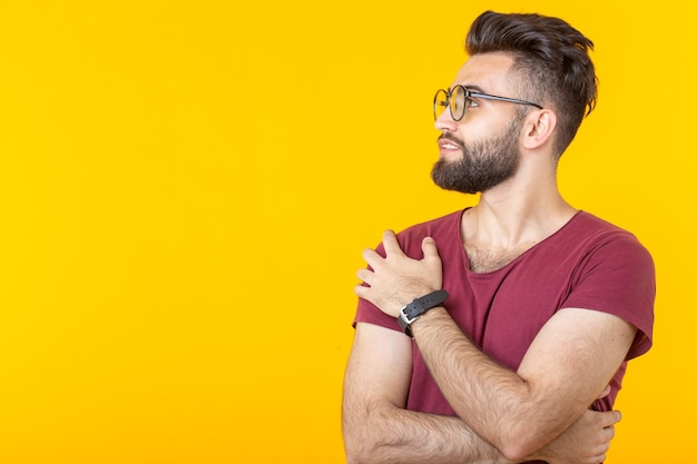 Portrait of a handsome arab young male student in burgundy shirt posing on a yellow wall