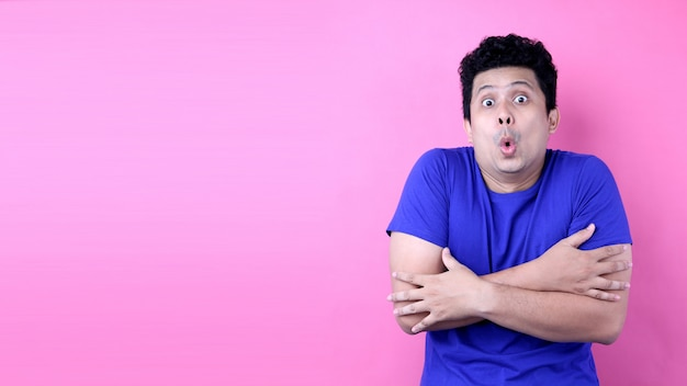 Portrait handsome asia man feeling cold on pink background in studio