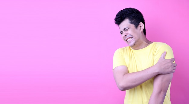 Portrait of a handsome asia man, holding his shoulder in pain on pink background in studio