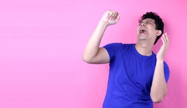 Portrait handsome asia man singing loud while standing  on pink background in studio