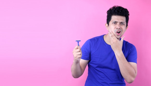 Portrait handsome asia man with a shaving on pink background in studio