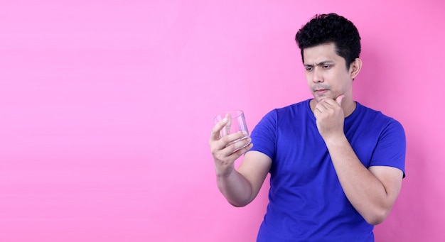 Портрет красивый азиатских мужчин хотят бросить пить алкоголь на розовом фоне в студии