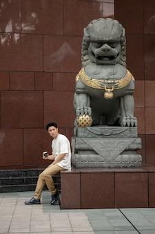 Ritratto di un bell'uomo asiatico in città che beve una tazza di caffè accanto alla statua