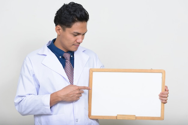 Portrait of handsome asian man doctor holding white board