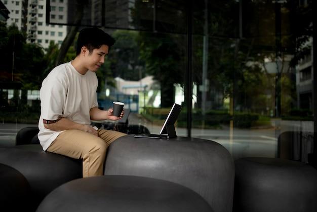 Ritratto di un bell'uomo asiatico che mangia caffè all'aperto in città