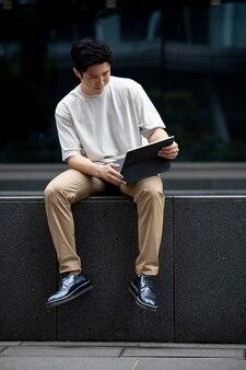 Ritratto di un bell'uomo asiatico che usa il portatile all'aperto in città