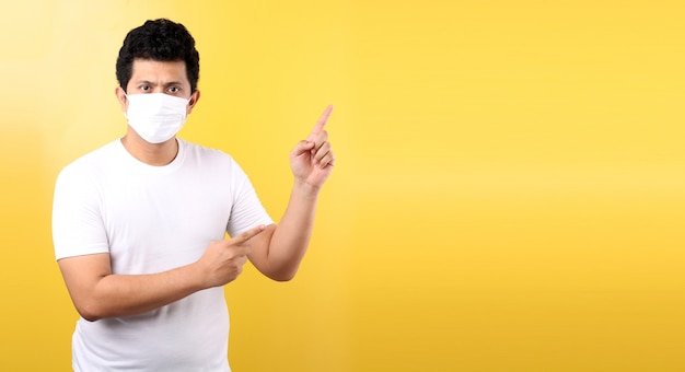 Portrait of handsome  asian man wearing a mask is sick pointing finger isolated