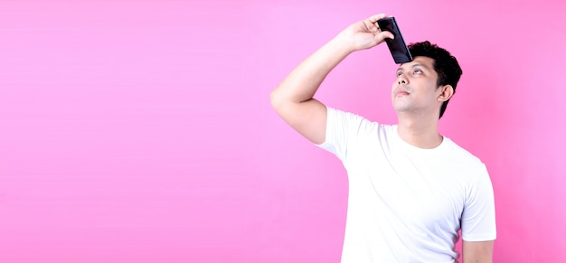 Portrait of handsome asian man with dreamy look, thinking while holding smartphone,on pink wall.