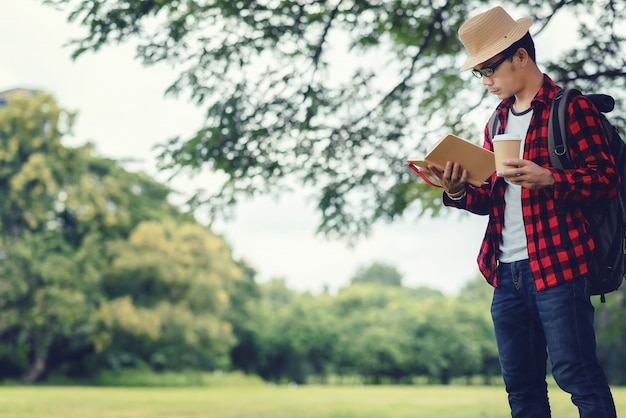 Portrait of handsome asian tourist man wearing glasses reading a book at the park on a summer day.