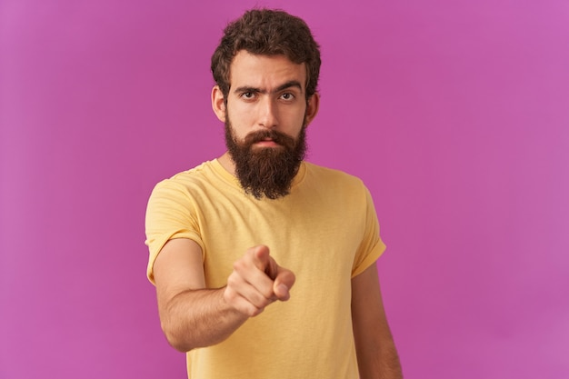 Portrait of handsome attentive young guy bearded is pointing finger at front looking at you mindful paying attention