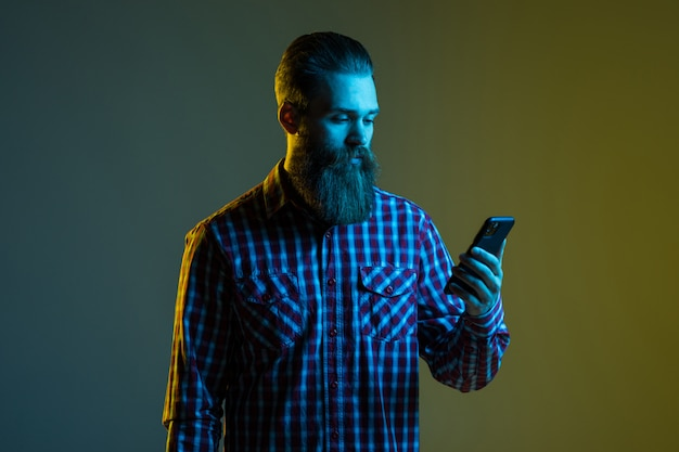 Portrait of a handsome attractive bearded man with earphones holding mobile phone isolated on the light space