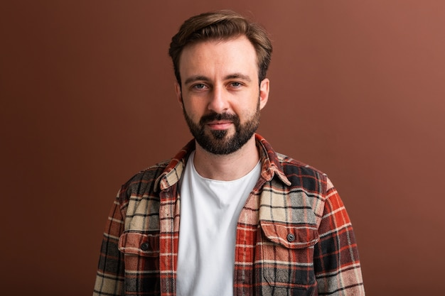 Portrait of handsome attractive stylish bearded man on brown