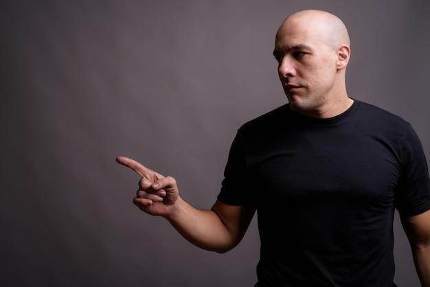 Portrait of handsome bald man against gray background