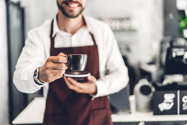 Portrait of handsome bearded barista man small smiling and holding cup of coffee in the cafe