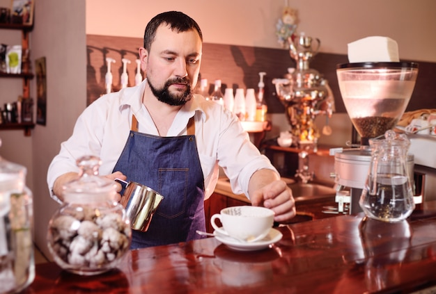 Portrait of a handsome bearded barista preparing coffee on the background of a coffee house