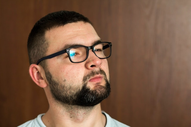Portrait of handsome bearded black haired intelligent modern young man in glasses with short haircut and kind black eyes smiling on blurred background. youth and confidence concept.