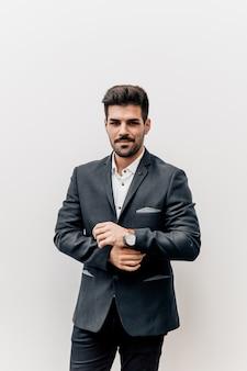 Portrait of handsome bearded businessman on light gray background.