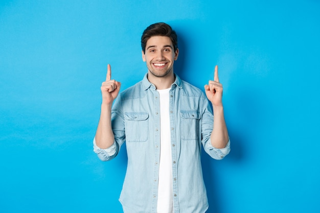 Portrait of handsome bearded man in casual outfit, smiling happy and pointing fingers up at copy space, standing over blue background