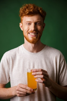 Portrait of handsome bearded man holding glass of orange juice