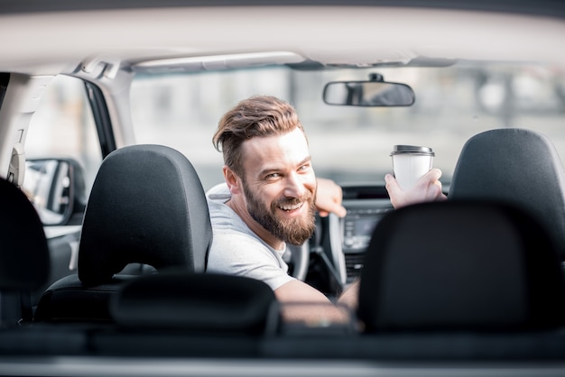 Portrait of a handsome bearded man looking back sitting on the front seat of the car with cup of coffee