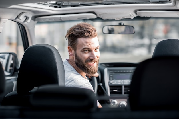 Portrait of a handsome bearded man looking back sitting on the front seat of the car