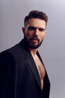 Portrait of a handsome bearded man posing in black suit, with bare torso