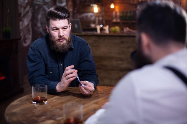 Ritratto di un bell'uomo barbuto che mescola le carte da gioco in un pub. bicchiere di whisky, uomo alla moda. uomo elegante.