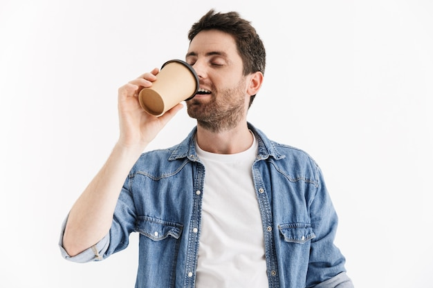 Portrait of a handsome bearded man wearing casual clothes standing isolated, drinking takeaway coffee