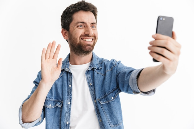 Portrait of a handsome bearded man wearing casual clothes standing isolated, taking a selfie