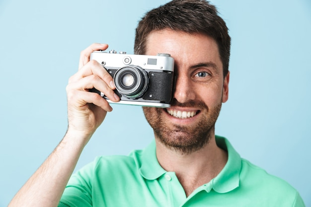 Portrait of a handsome bearded man wearing casual clothing standing isolated over blue wall, taking a picture with photo camera