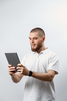 Portrait of a handsome bearded man in a white t-shirt talking video calling tablet