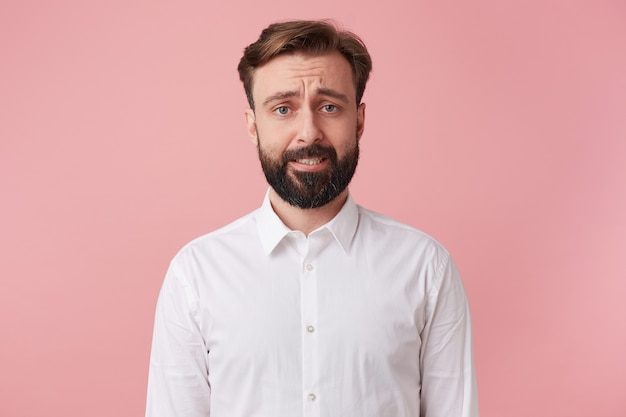 Portrait of a handsome bearded man who is regretful that has just destroyed a house of cards. frown and looking at camera isolated pink background.