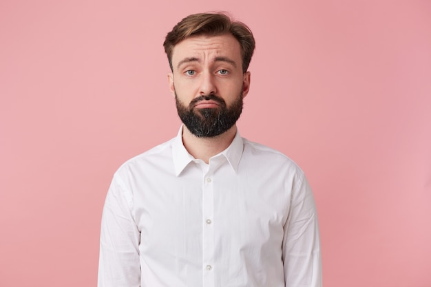 Portrait of a handsome bearded man who is upset about something, wearing a white shirt. looking at camera with sullen facial expression isolated over oink background.