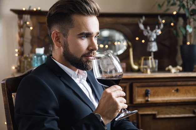 Portrait of handsome bearded man with a glass of red wine