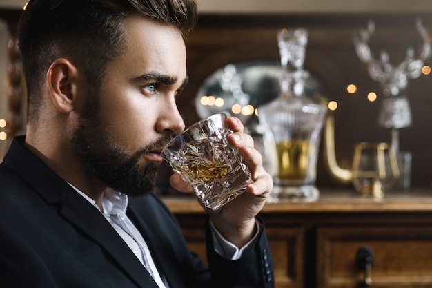 Portrait of handsome bearded man with a glass of whiskey