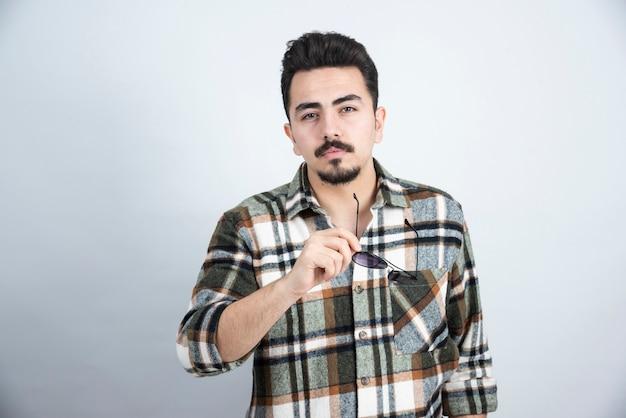 Ritratto di uomo barbuto bello con gli occhiali in posa e in piedi sul muro bianco.
