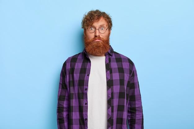 Il ritratto dell'uomo dai capelli rossi barbuto bello guarda sorprendentemente alla macchina fotografica