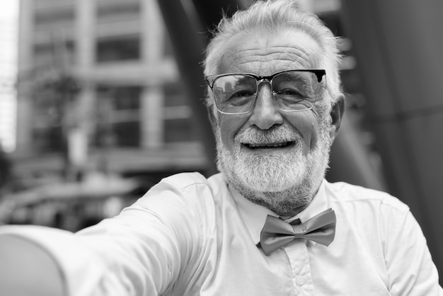 Portrait of handsome bearded senior tourist man wearing stylish clothes while exploring the city of bangkok in black and white Premium Photo