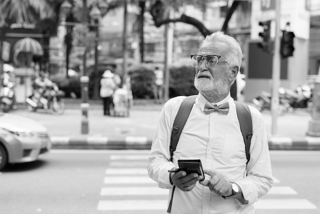 Portrait of handsome bearded senior tourist man wearing stylish clothes while exploring the city of bangkok in black and white