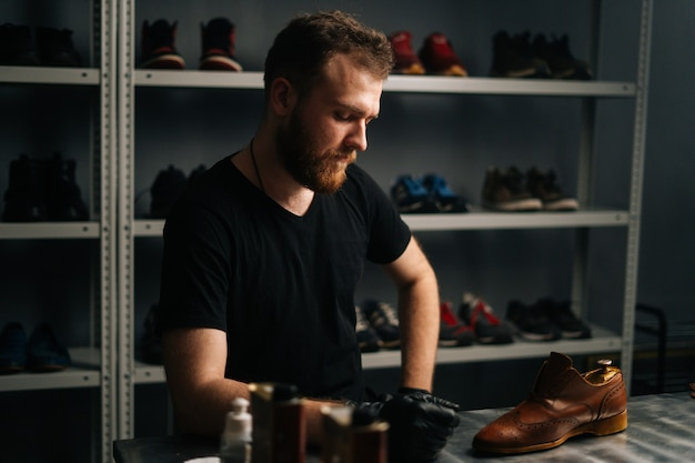 Portrait of handsome bearded shoemaker examining light brown leather shoes during restoration working