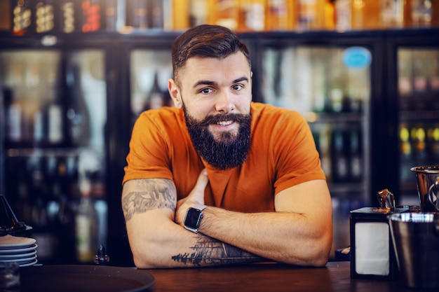 Portrait of handsome bearded smiling positive tattooed barman leaning on bar counter