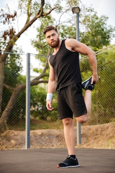 Portrait of a handsome bearded sportsman stretching legs outdoors