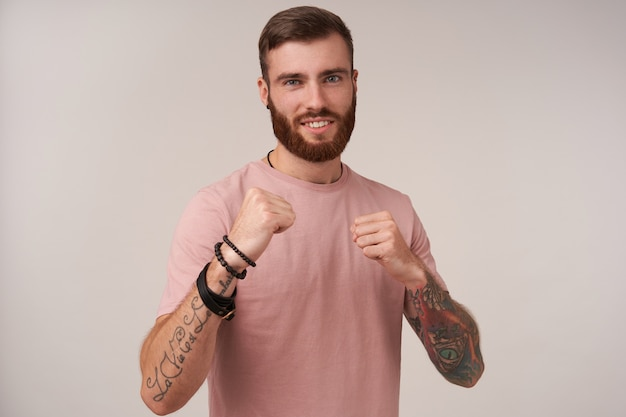 Portrait of handsome bearded tattooed guy with trendy haircut standing on white in defensive position with charming wide smile