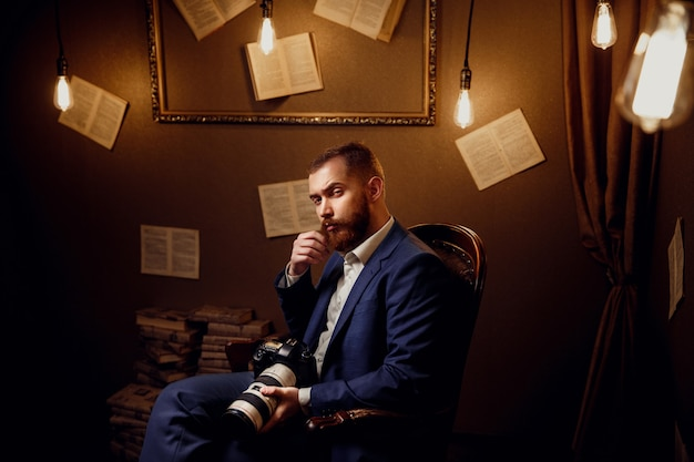 Portrait of handsome bearded young man wearing blue suit, white shirt sitting in luxury library hold camera. photographer, videographer.