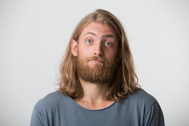 Il ritratto del giovane barbuto bello con capelli lunghi biondi indossa la maglietta grigia sembra serio e sicuro isolato sopra il muro bianco