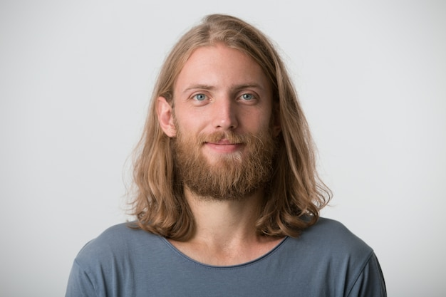 Portrait of handsome bearded young man with blonde long hair wears grey t shirt looks serious and confident isolated over white wall