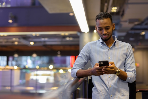 Portrait of handsome black african businessman inside shopping mall texting with mobile phone horizontal shot
